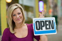 "Shopkeeper hold an ""open"" sign."